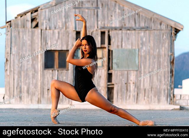 Ballerina dancing in front of wooden hut
