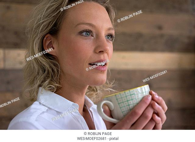 Young businesswoman holding cup of coffee looking sideways