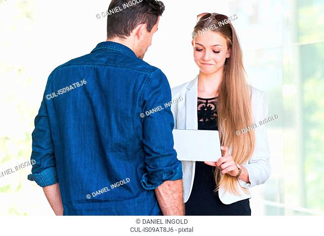 Young couple using digital tablet in front of window in city