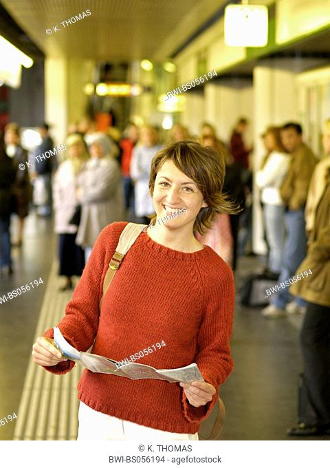 young woman / twen, waiting on a sub way station with a city map in her hands, laughing