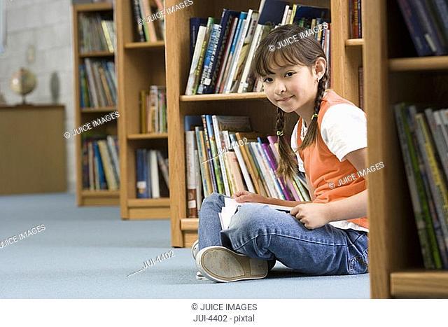 Girl 10-12 sitting on floor beside bookshelf in library, reading book, smiling, side view, portrait
