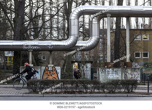Silver pipes run along a path in Berlin, Germany