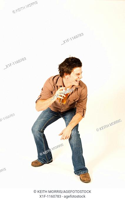 Happy young man drinking a pint of beer lager