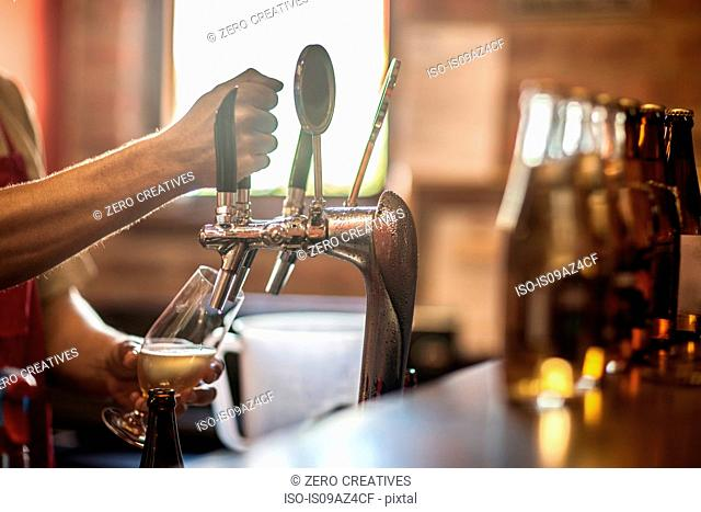 Hands of bartender pulling beer pump