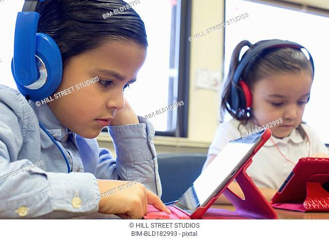 Caucasian students using digital tablets in classroom