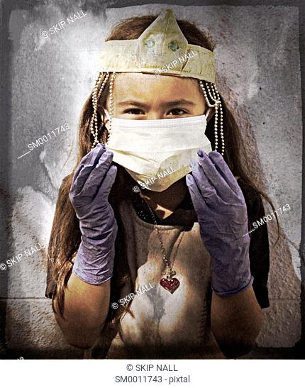 7 year od girl dressed in crown and surgical mask and gloves prretending to be a surgeon