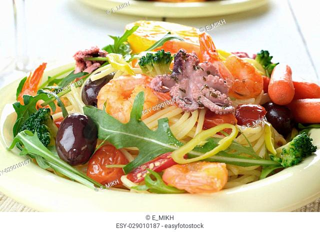 Seafood spaghetti pasta dish with octopus, shrimps, cherry tomatoes and olives