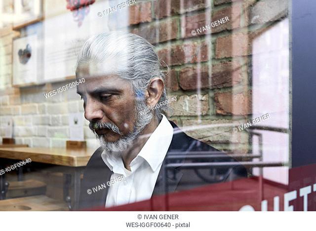 Senior businessman behind windowpane in a coffee shop