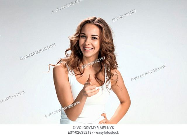 The young happy woman pointing his finger at the camera on gray background
