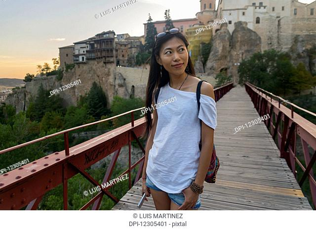 Young Chinese woman walking around Cuenca's downtown; Cuenca, Castile-La Mancha, Spain