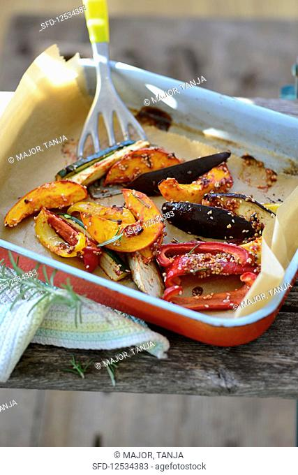 Oven-roasted vegetables with sesame seeds in a baking dish