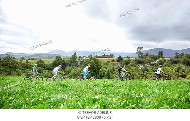 Friends mountain biking in idyllic, remote field