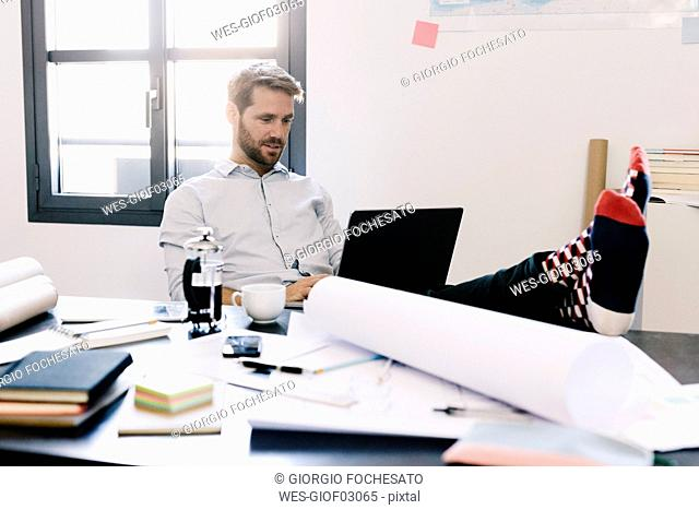Portrait of smiling architect sitting with feet up at desk using laptop