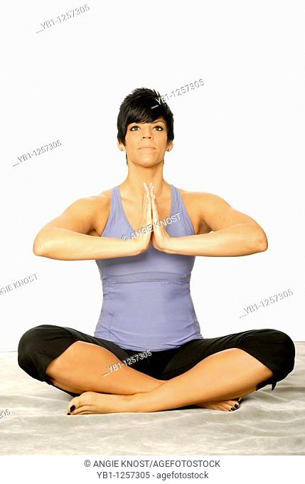 Attractive woman in yoga pose, wearing exercise clothing