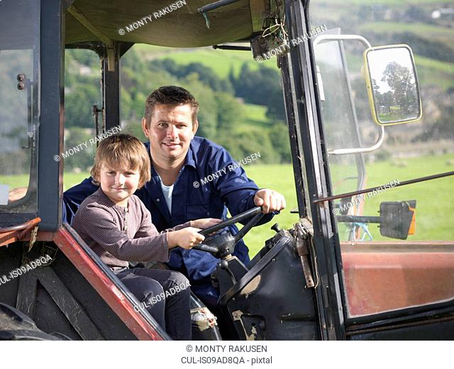 Farmer and young son in tractor in field, portrait