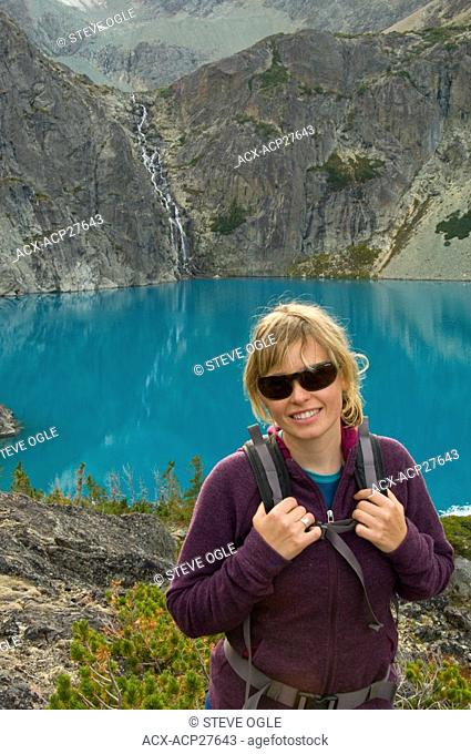 A young, attractive woman with sunglasses smiles in front of a turquoise blue lake and waterfall in the Coast Mountains, British Columbia, Canada