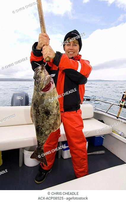 Woman displays halibut while Sport fishing at Langara Island Lodge, Queen Charlotte Islands, British Columbia, Canada