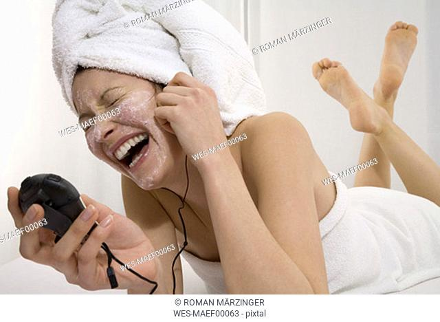 Woman with MP3-player lying on bed with towel on head