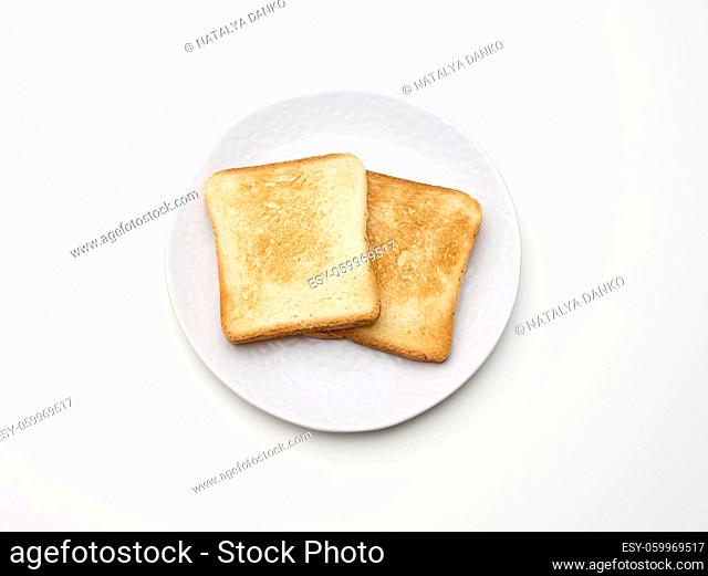 square pieces of toasted bread made from white wheat flour on a round plate. White table background