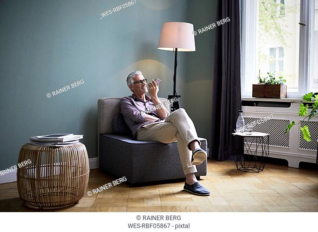 Mature man using cell phone at home