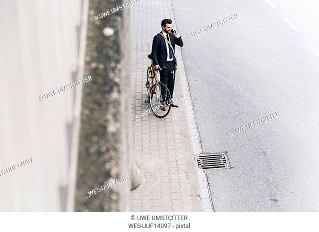 Businessman with bicycle on cell phone at the street