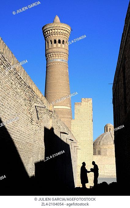 Silhouette of two men shaking hands in a small street near Kalon minaret. Uzbekistan, Bukhara