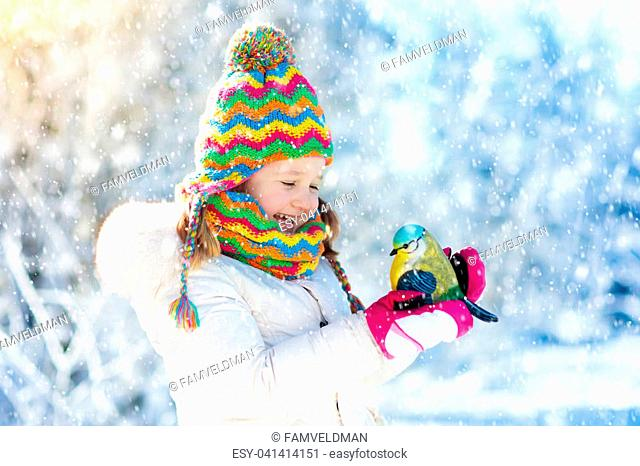 Child feeding tit bird in winter park. Kids feed birds in snowy forest. Little girl with titmouse. Kids watch wild animals. Family Christmas vacation