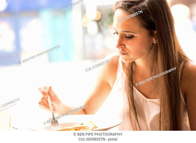 Young woman eating lunch in restaurant