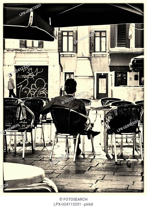 Quiet moment: back view of a man sitting at an open cafe with single man walking near graffitti covered doorway, Campo Santa Margherita, monochrome image