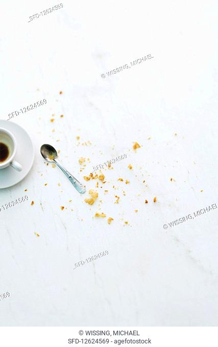 Croissiant crumbs next to an empty espresso cup