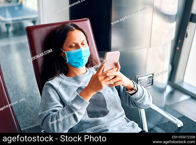 Woman in virus protection face mask rest with smartphone in the departure lounge in international airport
