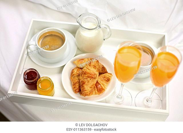 food, breakfast and eating concept - close up of tray with croissants, coffee, milk and two glasses of orange juice in bed