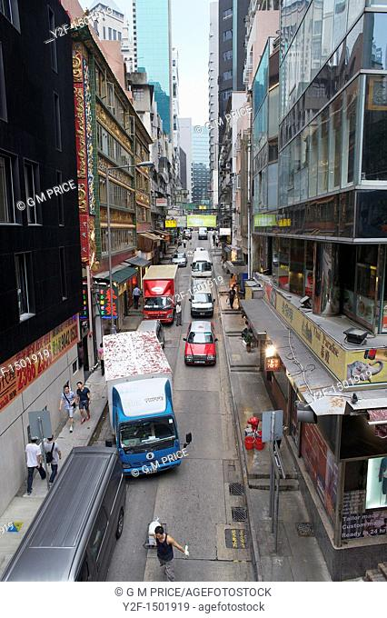 pedestrians and traffic in narrow commercial street, Central district, Hong Kong, China