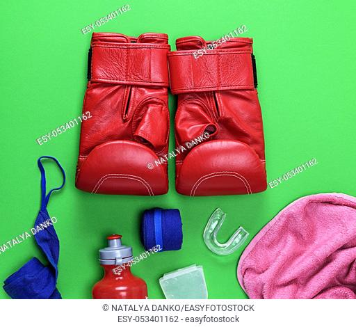 red leather boxing gloves, a plastic water bottle and a pink towel and blue textile bandage on a green background