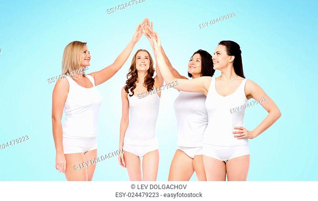 gesture, friendship, beauty, body positive and people concept - group of happy different women in white underwear making high five over blue background