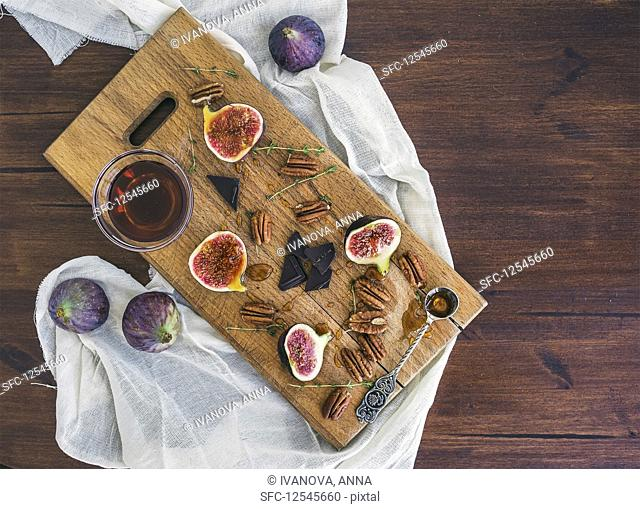 Fresh figs, bitter chocolate and pekan nuts with honey on a wooden board and white tissue