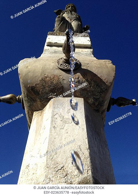 Close-up of an old stone fountain with dripping water and blue sky background. Low angle