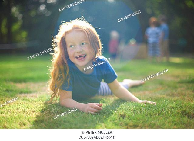 Happy young girl lying on grass in garden