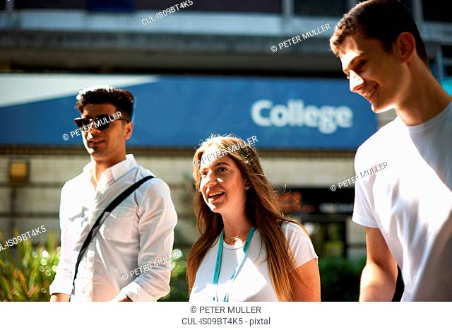 Teenage girl with young male higher education students leaving college campus