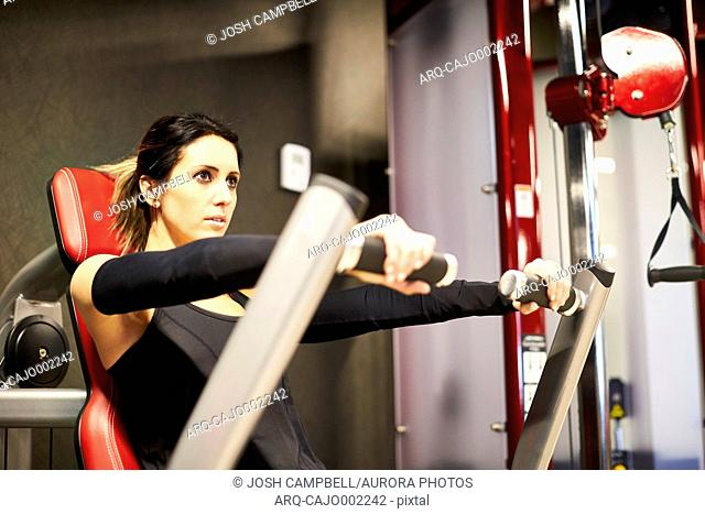 Side view shot of a woman working out on a chest press machine at the gym