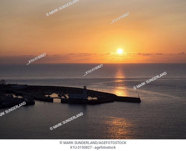 Sun rising over the North Sea at the harbour in Scarborough North Yorkshire England