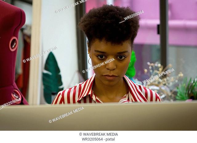 Fashion designer using computer in fashion studio