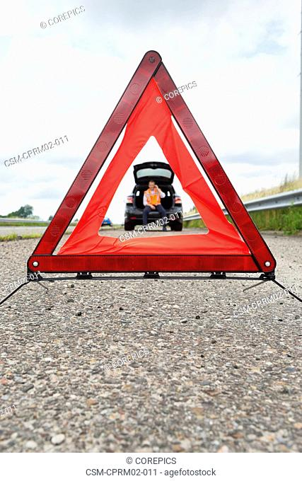 Warning tiangle on the side of a motorway, with a motorist calling for assistance in the car in the background. Focus on the triangle