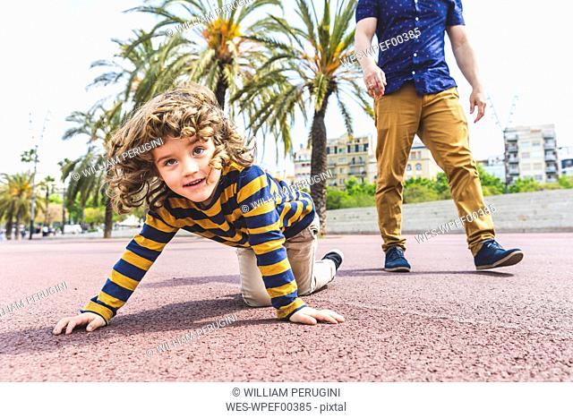 Spain, Barcelona, young boy crawling next to his father on seaside promenade