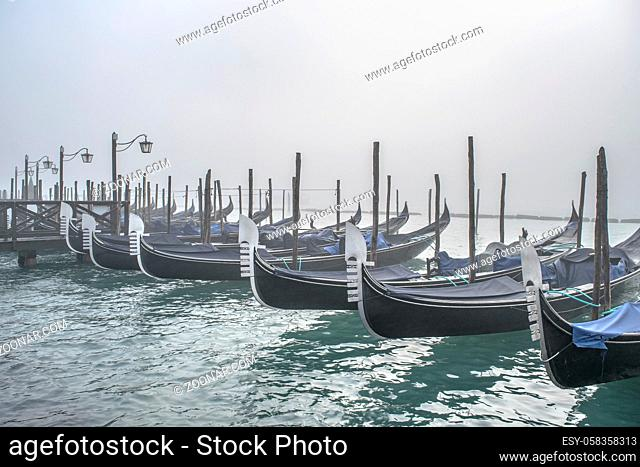 Winter morning scene group of gondolas parked at shore in venice city, Italy