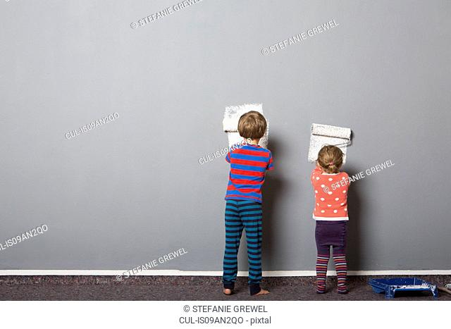 Rear view of brother and toddler sister beginning to paint wall