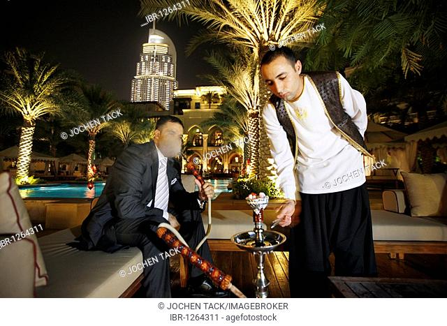 Man smoking a water pipe, shisha, by the pool in the evening, The Palace Hotel, Oldtown Dubai, United Arab Emirates, Middle East