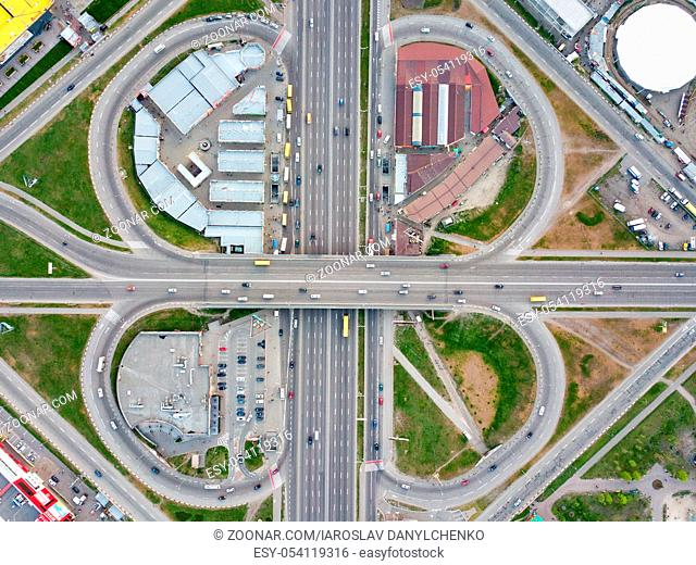 Aerial view district Poznyaki, road junction with passing cars, parking, green area and buildings in sity Kiev, Ukraine. Photo from the drone
