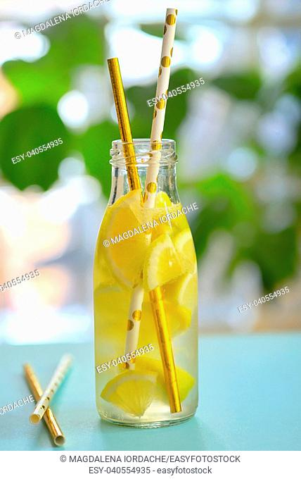 Bottle of water and lemon on table
