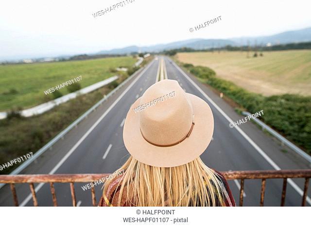 Woman on bridge looking at motorway